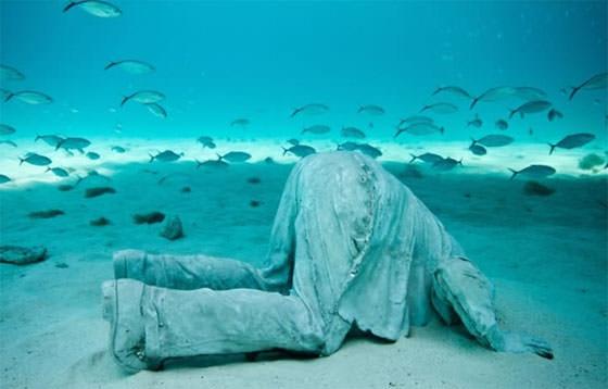 скульптура мужчины, прячущего голову в морской песок