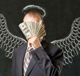 мужчина в костюме с крыльями держит пачку доларов